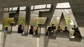 Jornalistas refletem no logotipo da Fifa na sede da entidade em Zurique, na Suíça. 04/10/2013 REUTERS/Arnd Wiegmann