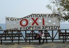 """A woman sits on a bench below a banner that reads """"Ouranoupoli says no to gold mining"""" at Ouranoupoli village, where more than 80 percent of locals oppose the gold mine project, in Halkidiki region, northern Greece, in this picture taken August 15, 2013. REUTERS/Lefteris Papadimas"""