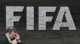 A reporter uses his cell phone as he walks past a FIFA logo in front of FIFA headquarters in Zurich in this file photo taken on October 29, 2007. REUTERS/Michael Buholzer