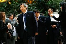 China Central Bank Deputy Governor Yi Gang walks to a family photo after a meeting of G-20 finance ministers and central bank governors during the IMF-World Bank annual meetings in Washington October 10, 2014.  REUTERS/Jonathan Ernst