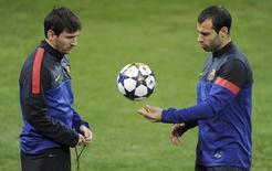 Lionel Messi e Javier Mascherano durante treino do Barcelona, em foto de arquivo. 19/02/2013  REUTERS/Stringer