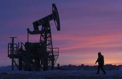 Un trabajador camina frente a una extractora de petróleo en un campo de crudo cerca de Nikolo-Berezovka. Imagen de archivo, 28 enero, 2015.  Las tres mayores agencias de energía del mundo pronosticaron una mayor demanda del petróleo de la OPEP este año, en una señal de  la estrategia del grupo de dejar que los precios caigan está dando resultados al hacer que sus rivales reduzcan su producción y pierdan participación de mercado. REUTERS/Sergei Karpukhin