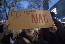 """REFILE - CORRECTING TYPO  A protester holds a placard to demonstrate against """"Fifty Shades of Grey"""" at the film's UK premiere in London, February 12, 2015. REUTERS/Neil Hall"""