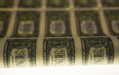 Una lámina de billetes de dólar durante su proceso de producción fotografiada en Washington. Imagen de archivo, 14 noviembre, 2014.  El dólar recortó la mayor parte de sus ganancias frente a una canasta de las principales monedas el miércoles, después de que las minutas de la reunión de enero de la Reserva Federal fueron consideradas como moderadas, mientras que el optimismo sobre Grecia le dio cierto respaldo al euro. REUTERS/Gary Cameron