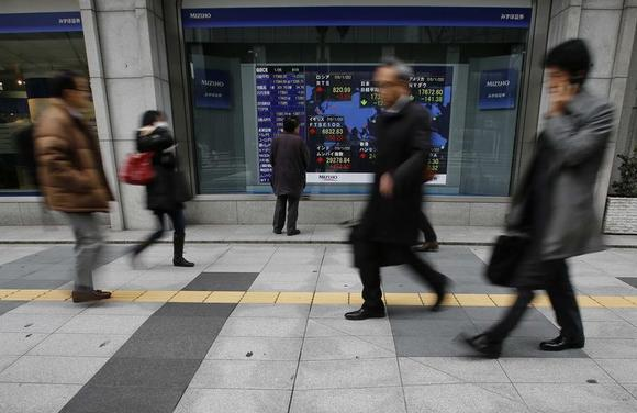 A man looks at an electronic board showing the stock market indices of various countries outside a brokerage in Tokyo January 26, 2015. REUTERS/Yuya Shino