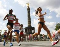 Julia Mumbi Muraga of Kenya (L) runs ahead of Nailiya Yulamanova of Russia and Bezunesh Bekele of Ethopia ( 3rd L) past the Victory Column (Siegessaeule) during women's marathon at the world athletics championships in central Berlin August 23, 2009.       REUTERS/Phil Noble