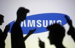 Silhuetas de pessoas com telefones em frente a um logotipo da Samsung, em foto ilustração. 29/10/2014 REUTERS/Dado Ruvic