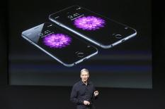 Apple CEO Tim Cook stands in front of a screen displaying the IPhone 6 during a presentation at Apple headquarters in Cupertino, California October 16, 2014.  REUTERS/Robert Galbraith