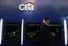 Un hombre camina frente cajeros de Citigroup en Manhattan, New York. Imagen de archivo, 16 octubre, 2012.  Citigroup Inc redujo el salario del presidente ejecutivo Michael Corbat en cerca de un 10 por ciento en 2014, un año en que las ganancias del banco casi se redujeron a la mitad debido a mayores costos legales y a una caída en las transacciones en bonos. REUTERS/Carlo Allegri