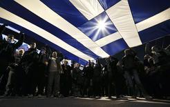 Lors d'une manifestation contre l'austérité devant le Parlement à Athènes, le week-end dernier. Le Premier ministre grec Alexis Tsipras a déclaré samedi que l'accord conclu la veille à Bruxelles sur une prolongation sous conditions de l'aide financière à Athènes revenait à annuler les engagements pris par les gouvernements précédents en matière d'austérité. /Photo prise le 15 février 2015/REUTERS/Alkis Konstantinidis
