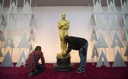Trabajadores en el Teatro Dolby de Los Angeles colocan una estatua dorada del Oscar en los preparativos para la ceremonia de la Academia. Febrero 22, 2015. REUTERS/Mario Anzuoni