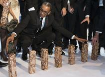 """Director Abderrahmane Sissako (C) kneels near the trophies received for the film """"Timbuktu"""" at the 40th Cesar Awards ceremony in Paris February 20, 2015. REUTERS/Philippe Wojazer"""