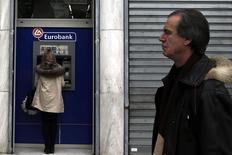 Una mujer retira dinero en un cajero automático de Eurobank en Atenas, feb 23 2015. Los retiros de depósitos de los bancos griegos ascendieron la semana pasada a cerca de 3.000 millones de euros, según la estimación de JP Morgan, elaborada antes del acuerdo para extender el rescate de Atenas anunciado el viernes con los acreedores de la zona euro. REUTERS/Alkis Konstantinidis