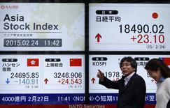 Peatones caminan frente a un tablero electrónico que muestra los índices bursátiles de varios países de Asia fuera de una casa de valores en Tokio, 24 de febrero del 2015. Los mercados de valores de Asia subían el martes y la bolsa de Tokio tocó un máximo en 15 años, aunque las ganancias eran limitadas en momentos en que los inversores aguardan el testimonio que la presidenta de la Reserva Federal de Estados Unidos, Janet Yellen, ofrecerá ante el Congreso de su país. REUTERS / Yuya Shino