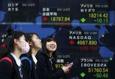 Foto de archivo: Unas estudiantes pasan junto a un tablero electrónico que muestra el índice Nikkei de Japón (arriba al centro) y el índice de precio de las acciones de varios países fuera de una casa de valores en Tokio, 27 de febrero de 2015. Las bolsas de Asia subían el lunes luego de que el recorte de las tasas de interés en China durante el fin de semana contrarrestó parcialmente unos datos débiles de Estados Unidos, y el dólar tocó un máximo en 11 años contra una canasta de monedas. REUTERS / Toru Hanai