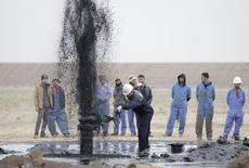 Trabajadores junto a una tubería de transporte de crudo en el campo Al Tuba en Basra, Irak, feb 19 2015. Irak dijo el lunes que revisará sus acuerdos de producción de petróleo con firmas internacionales porque la caída de los precios del crudo hace que los costos de los actuales contratos financieros sean demasiado altos. REUTERS/Essam Al-Sudani