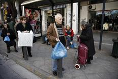 People carrying goods wait at a bus stop in Athens' commercial district March 2, 2015. REUTERS/Alkis Konstantinidis