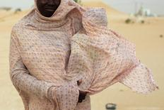 A woman shields her child from the wind while walking on sand dunes in Nouakchott June 22, 2014. REUTERS/Joe Penney