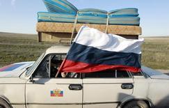 Автомобиль с российским флагом близ Феодосии. 24 марта 2014 года. Вошедший год назад в состав России Крым не имеет сухопутного сообщения с основной территорией страны и вынужден создавать запасы важнейших ресурсов, в частности энергоносителей, или пытаться производить их самостоятельно. REUTERS/Shamil Zhumatov