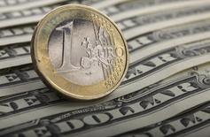 Монеты валюты евро на долларовых купюрах в Варшаве 26 января 2011 года. Курс евро к доллару близок к 11-летнему минимуму, пока инвесторы ждут от Европейского центробанка подробностей программы скупки облигаций. REUTERS/Kacper Pempel
