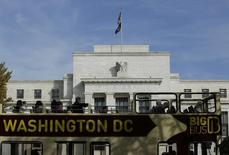Туристический автобус проезжает мимо здания ФРС в Вашингтоне. 28 октября 2014 года. Все американские банки прошли проверку на то, как они справятся со следующим экономическими кризисом, сообщила в четверг ФРС США, но банки с большими торговыми портфелями показали себя слабыми из-за появления новых элементов в процедуре проверки. REUTERS/Gary Cameron