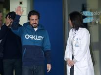 McLaren's Formula One driver Fernando Alonso of Spain waves to the media as he leaves the hospital where he was hospitalized in Sant Cugat after crashing during a test session February 25, 2015. REUTERS/Albert Gea