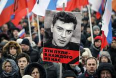 """A portrait of Kremlin critic Boris Nemtsov, who was shot dead on Friday night, is seen during a march to commemorate him in central Moscow March 1, 2015. Holding placards declaring """"I am not afraid"""", thousands of Russians marched in Moscow on Sunday in memory of Nemtsov, whose murder has widened a split in society that some say could threaten Russia's future. The words under the portrait reads """"These bullets are meant for each of us"""". REUTERS/Maxim Shemetov (RUSSIA - Tags: CRIME LAW POLITICS CIVIL UNREST)"""