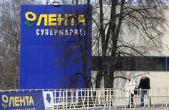 Прохожие у супермаркета Лента в Москве. 3 февраля 2014 года. Один из крупнейших в РФ продуктовых ритейлеров - Лента во втором полугодии 2014 года увеличила чистую прибыль на 39 процентов до 6,4 миллиарда рублей в годовом выражении, сообщила компания в четверг. REUTERS/Maxim Shemetov