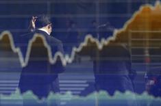 Экран брокерской конторы в Токио с графиком японского индекса Nikkei. 12 марта 2015 года. Азиатские фондовые рынки, кроме Южной Кореи, выросли в четверг благодаря местным новостям. REUTERS/Toru Hanai