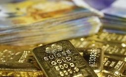 Imagen de archivo de barras de oro y francos suizos ordenados para una ilustración fotográfica en Viena, nov 13 2014. El oro se mantuvo estable el jueves gracias a que una depreciación del dólar desde máximos en 12 años frenó una caída que llevaba ocho sesiones, aunque especulaciones de que las tasas de interés en Estados Unidos subirán más temprano que tarde dejaron a los precios bajo presión.       REUTERS/Leonhard Foeger