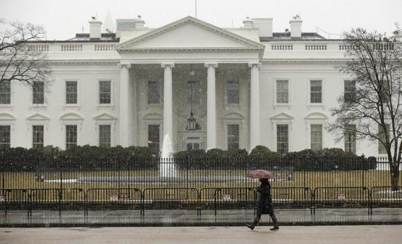 Snow starts to fall as a woman walks past the White House in Washington March 5, 2015. REUTERS/Kevin Lamarque