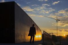 A man walks along the embankment of the river Spree during sunset in Berlin, September 13, 2013.   REUTERS/Thomas Peter