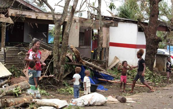 A woman carrying a baby stands with children outside homes damaged by Cyclone Pam, on a street surrounded by debris in Port Vila, the capital city of the Pacific island nation of Vanuatu March 15, 2015.   REUTERS/Kris Paras