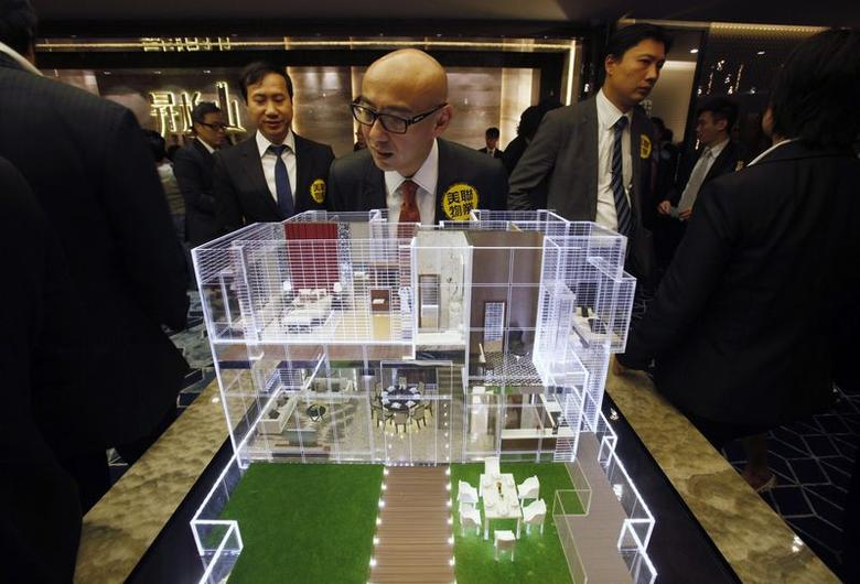 A property sales agent looks at a penthouse unit model of ''The Rise'', the latest development released by Cheung Kong Holdings Ltd., at a promotional event in Hong Kong in this September 5, 2013 file photo.  REUTERS/Bobby Yip/Files