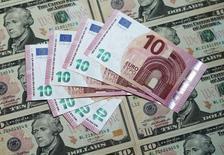 Ilustración que muestra billetes de dólares y euros en Viena. 16 de marzo, 2015.  El regulador de divisas chino incrementará el seguimiento de las transacciones en moneda extranjera equivalentes o superiores a  10.000 dólares, después de detectar que los bancos no se están adhiriendo del todo a las actuales normas, dijeron el jueves dos fuentes de la industria. REUTERS/Heinz-Peter Bader