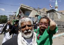 Мужчина с ребенком у мечети, в которой произошел взрыв, в Сане. 20 марта 2015 года. По меньшей мере 46 человек погибли и 200 получили ранения в результате взрывов, устроенных четырьмя смертниками в двух мечетях столицы Йемена Саны во время пятничной молитвы, сообщили источники в службах безопасности Йемена и медики. REUTERS/Khaled Abdullah