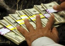 U.S. dollars are counted out by a banker at a bank in Westminster, Colorado November 3, 2009.  REUTERS/Rick Wilking