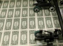 Plantillas con billetes de un dólar en su producción en la Casa de la Moneda de Estados Unidos en Washington, nov 14 2014. El dólar repuntaba contra el euro el martes por la persistente sensación alcista en favor de la moneda estadounidense, atada a la divergencia entre las políticas monetarias de Estados Unidos y Europa.    REUTERS/Gary Cameron