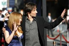 "Cast members David Duchovny (R) and Gillian Anderson wave at fans at the movie premiere of ""The X-Files: I Want to Believe"" at the Grauman's Chinese theatre in Hollywood, California July 23, 2008. REUTERS/Mario Anzuoni"