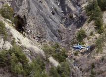 Вертолет над местом крушения самолета Airbus A320 во Французских Альпах. 25 марта 2015 года. Записи переговоров в кабине экипажа немецкого лайнера, упавшего в Альпах во вторник, указывают на то, что один из пилотов покинул кабину и не смог вернуться к штурвалу, сообщила газета New York Times. REUTERS/Emmanuel Foudrot