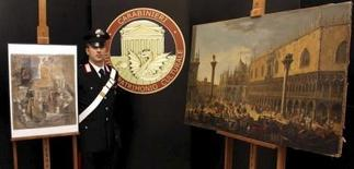 """A Carabinieri paramilitary policeman stands next to a painting of Luca Carlevarijs (R) and """"Violin e bouteille de bass"""" painting of Pablo Picasso during a news conference in Rome, in this March 27, 2015 handout picture provided by Carabineri Press Office.  REUTERS/Carabinieri Press Office/Handout via Reuters"""