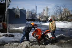 Unos trabajadores despejando nieve en el parque Brooklyn Bridge de Nueva York, feb 22 2015. El crecimiento económico de Estados Unidos se enfrió en el cuarto trimestre luego de que las ganancias corporativas después de impuestos fueran afectadas por la fortaleza del dólar, lo que incluso podría debilitar el gasto empresarial futuro. REUTERS/Eduardo Munoz