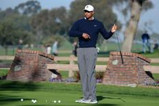Tiger Woods stretches on the putting green before the first round of the Farmers Insurance Open golf tournament during a fog delay at Torrey Pines Municipal Golf Course - South Co. Mandatory Credit: Jake Roth-USA TODAY Sports