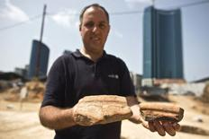 Diego Barkan, director of the excavation for the Israel Antiquities Authority (IAA), shows fragments of ancient basins unearthed at an archaeological dig in a future construction site in Tel Aviv March 29, 2015.  REUTERS/Nir Elias