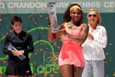 3Apr 4, 2015; Key Biscayne, FL, USA; Serena Williams celebrates with the Butch Buchholz Championship Trophy after her match against Carla Suarez Navarro (L) as tennis hall of famer Martina Navratilova (R) looks on in the women's singles final on day thirteen of the Miami Open at Crandon Park Tennis Center. Geoff Burke-USA TODAY Sports
