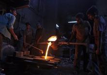 Trabalhadores despejam ferro derretido numa fábrica de autopeças, na Índia. 12/05/2014 REUTERS/Amit Dave