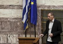 En la imagen, el ministro de Economía griego Yanis Varufakis pasa junto a las banderas de Grecia y la UE en la sesión del parlamento griego del 2 de abril de 2015. El ministro de Finanzas griego rechazó el domingo un reporte de un diario alemán que sostuvo que funcionarios de la zona euro quedaron impactados luego de que Atenas no lograra resumir sus planes para llevar a cabo reformas estructurales durante unas conversaciones en Bruselas. REUTERS/Alkis Konstantinidis