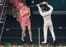 Lewis Hamilton, da Mercedes, joga champagne no rosto de moça no pódio do GP da China de F1, em Xangai. 12/04/2015 REUTERS/Carlos Barria