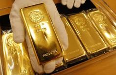 Сотрудник Tanaka Kikinzoku Jewelry K.K. демонстрирует слиток золота на складе компании в Токио. 29 января 2008 года. Цены на золото снижаются за счет укрепления доллара и подъема на европейских фондовых рынках. REUTERS/Issei Kato