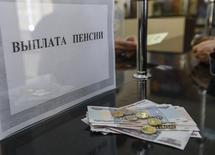 Окошко для выплаты пенсий на почте в Симферополе. 25 марта 2014 года. Министерство финансов России в попытке ускорить необходимое для бюджета решение о повышении пенсионного возраста нашло новые доводы в пользу непопулярного шага. REUTERS/Shamil Zhumatov